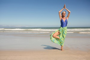 Senior woman practising yoga while standing against clear sky